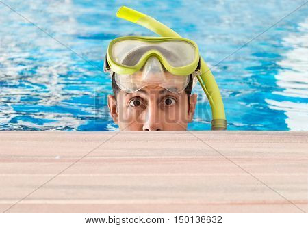 man emerging from a pool looking at camera and surprised by what is seen