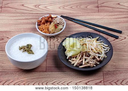 Rice gruel and fried mixed vegetable served side dish.  (topped roasted pumpkin kernel and  fried mushroom, bean sprouts,cabbage served side disk as bean cabba
