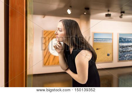 Woman closely scrutinizing a painting at an exhibition of the museum.Background photos are my property