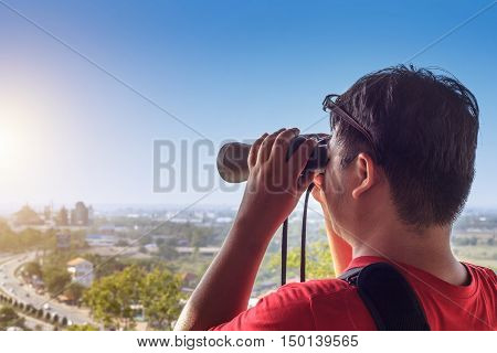 tourist looking through binoculars at distant city