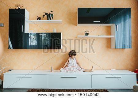 little girl sitting on twine (split) on furniture. training