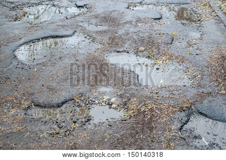 rough asphalt road with puddles and potholes