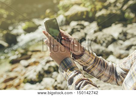 Female tourist using mobile smart phone for GPS navigation in outdoors nature on bright sunny day