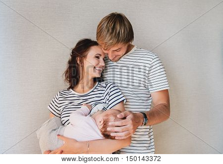 Happy family portrait - parents and their little cute baby girl. Mom breastfeeding newborn kid.