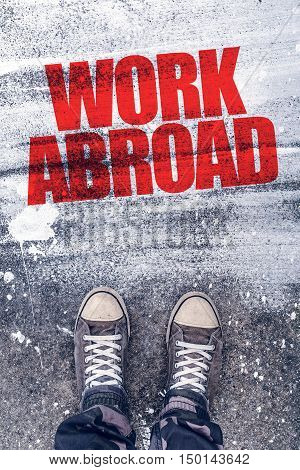 Work abroad title on the pavement above which is young male student standing and making decision to travel to foreign country and find a job