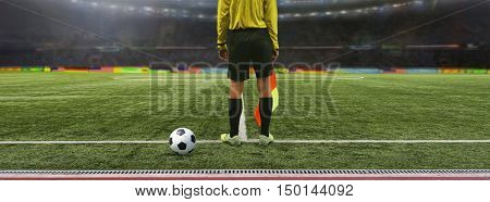 The referee soccer game stands on the field before the game, ready to blow the whistle