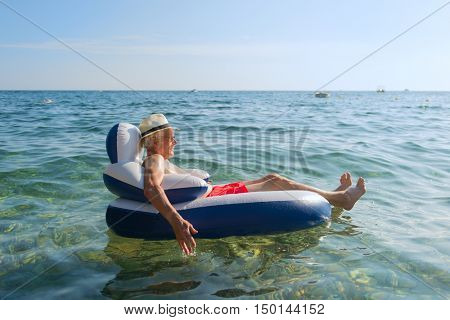 Senior man on vacation floating on chair in the sea