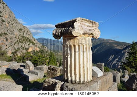 Ancient column in Ancient Greek archaeological site of Delphi shown at warm evening light Central Greece