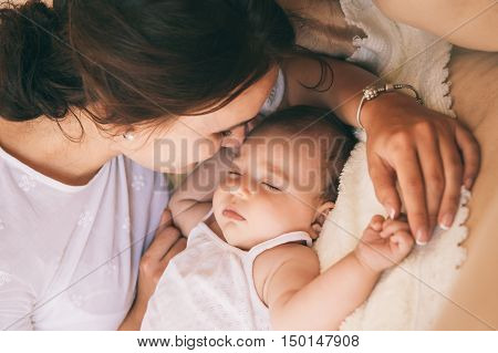 Beautiful young mom near sleeping 3 months baby.