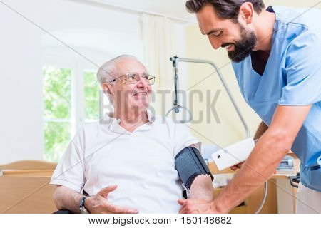 Nurse measuring blood pressure of senior patient
