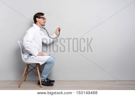 Happy to help. Concentrated handsome smiling doctor sitting on a chair and diagnosing his patient using a stethoscope.