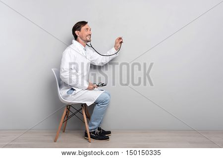 Here for you. Young happy ambitious doctor doing his work by using the stethoscope and diagnosing the patient