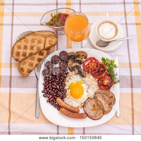 Full English fried breakfast with bacon, egg, sausages, black pudding, mushrooms, grilled tomatoes and baked beans. Closeup with toasts, coffee, orange juice and home made  red sauce.