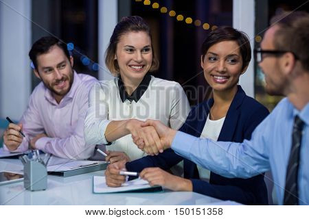 Businesspeople shaking hands in office at night
