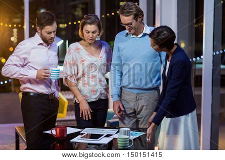 Businesspeople discussing on documents while having coffee in office