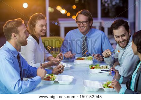 Group of businesspeople having meal in office at night