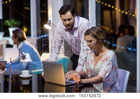 Businesswoman discussing with colleague over laptop in office