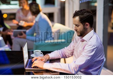 Attentive businessman working on laptop in office at night