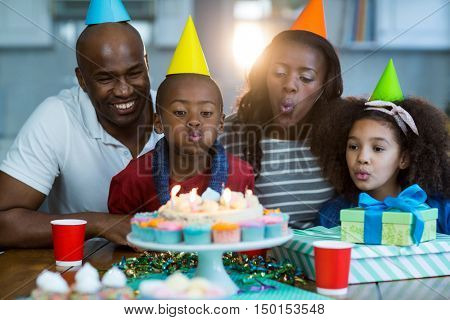 Family blowing out candles on birthday cake at home