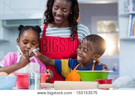 Children preparing cake with their mother in kitchen