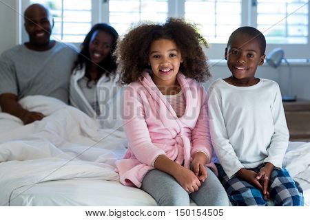 Children sitting on bed with parents in background at home