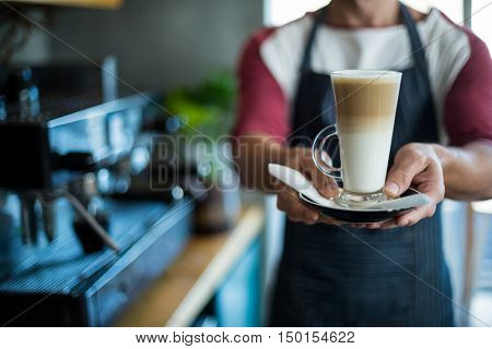 Mid-section of waiter holding cup of cold coffee at counter in cafe