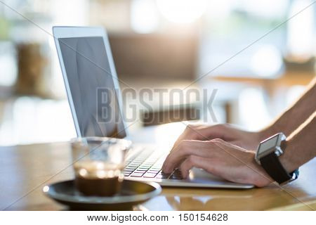Man using a laptop while having cup of coffee in cafe