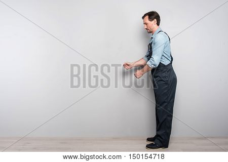 work hard. Pleasant diligent man standing against grey background and working while holding truck