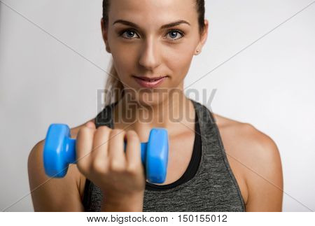 Young fitness woman making exercises with dumbbells