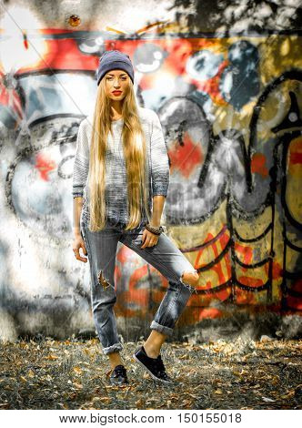 Fashionable Girl With Long Blond Hair In Stylish Clothes Standing On A Background Of Graffiti