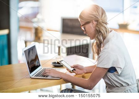 Woman using a laptop and mobile phone in caf\x92\xA9