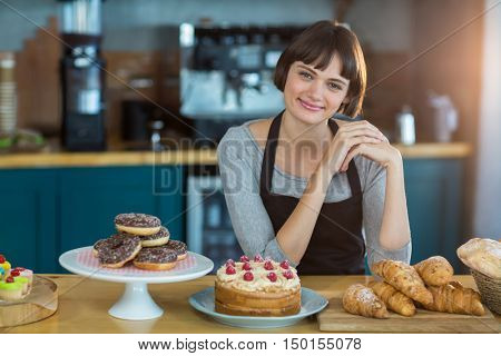 Portrait of waitress sitting at counter with sweet food on table in caf\x92\xA9