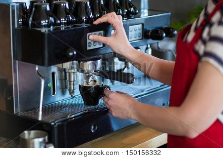 Mid-section of waitress making cup of coffee in caf\x92\xA9