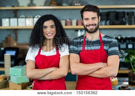 Portrait of smiling waiter and waitress standing at counter in cafe