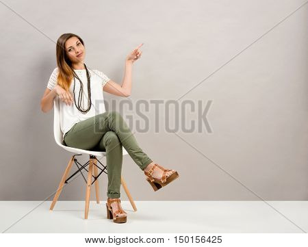 Woman sitting on a chair and pointing to the wall with copyspace for designers