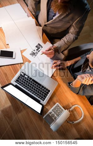 Businesswoman and colleague working at their desk in the office
