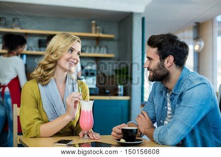 Couple interacting while having a cup of coffee and milkshake in caf\x92\xA9