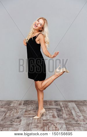 Playful pretty young woman with long hair in black dress posing on one leg isolated on a gray background