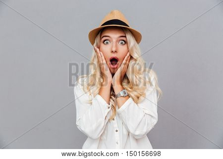 Surprised young woman in hat standing and looking at camera over gray background