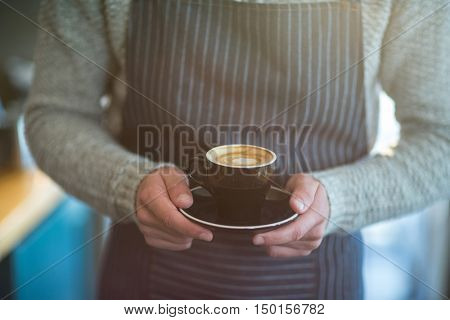 Mid-section of waiter holding cup of coffee in caf\x92\xA9