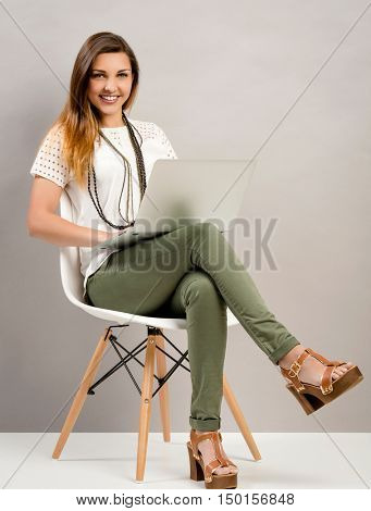 Beautiful woman sitting on a chair and working with a laptop