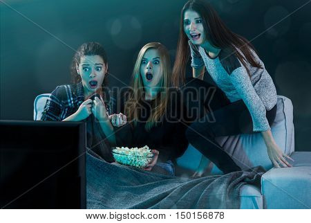 Teenage girls watching horror movie with popcorn
