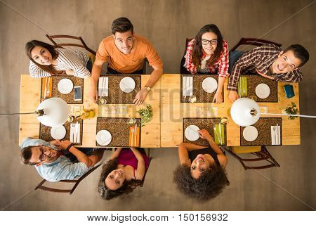 Group of people toasting and looking happy at a restaurant