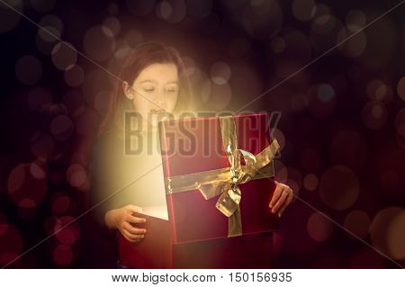 Little girl opening a magic box with light coming out