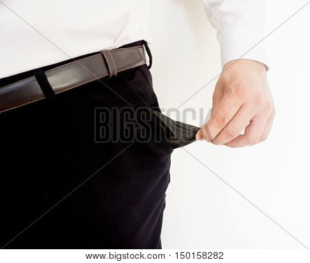 Business man showing his empty pockets on white background.