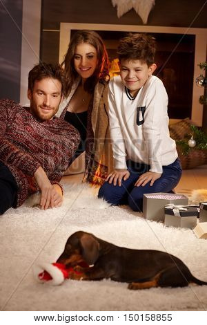 Young family watching dachshund puppy with love, receiving for christmas.