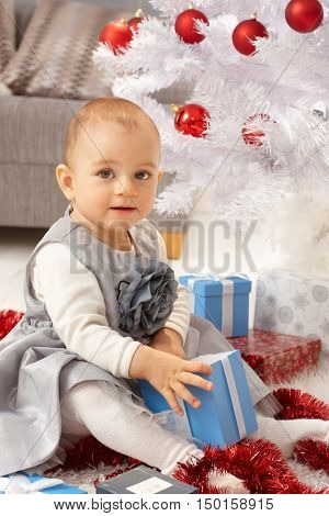 Cute little girl sitting by christmas tree, opening present, smiling.