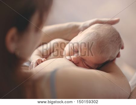 Mother breastfeeding her newborn child. Mom nursing baby.