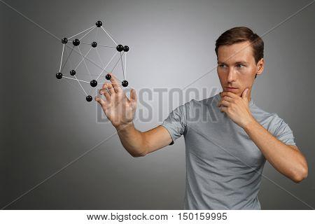Man scientist working with model of molecule or crystal lattice.
