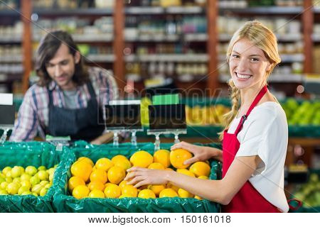 Portrait of smiling female staffs checking fruits in organic section of supermarket